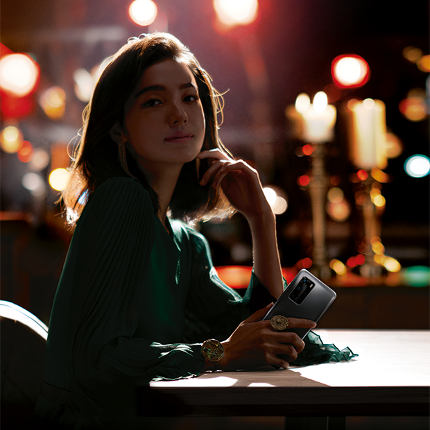 Girl at restaurant table with Huawei P40 phone in her hand