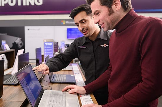 A Currys expert giving advice about a laptop to a customer.