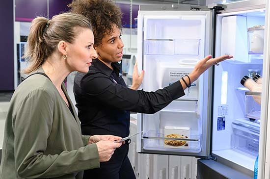 A Currys expert member showing a customer the inside of a fridge.