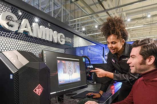 A Currys expert advising a customer on the latest gaming computer.