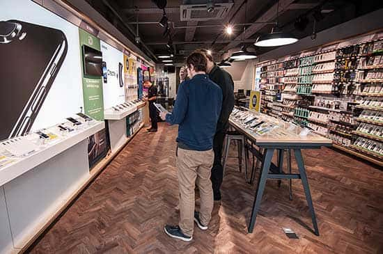 The inside of a Currys store. A member of staff helping a customer with a tablet.