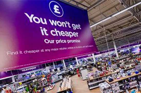 Inside of a Currys store, a giant banner with 'You won't get it cheaper' written on it hangs from the ceiling. Mobile version of image.