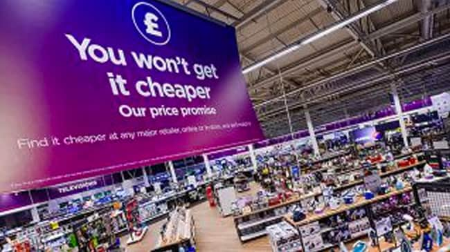 Inside of a Currys store, a giant banner with 'You won't get it cheaper' written on it hangs from the ceiling.