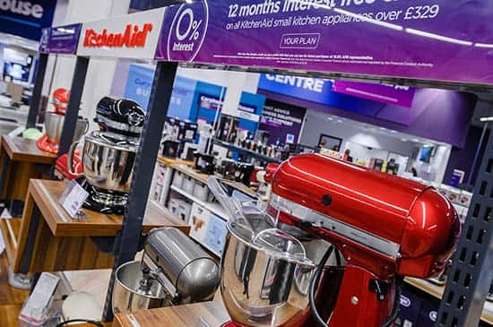 A range of different, brightly coloured food mixers on display, inside a Currys store.