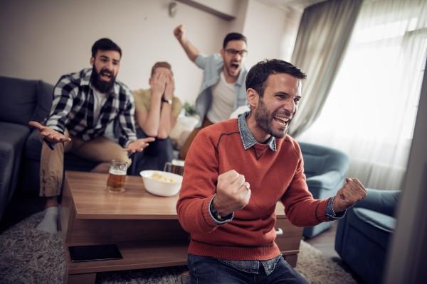 4 men celebrating watching the football