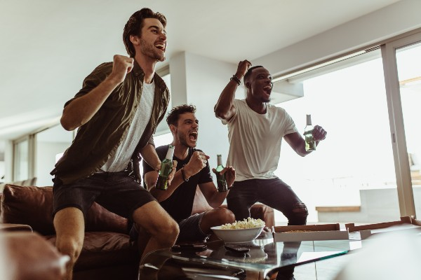 3 friends cheering watching the football
