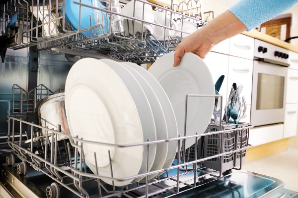 Plates and crockery stacked up inside a dishwasher.