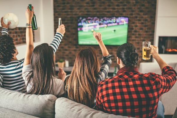 A group of friends on the sofa watching football