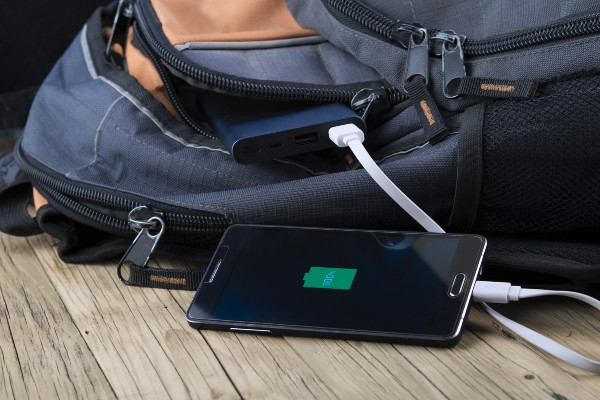 A backpack with a power bank poking out charging a phone