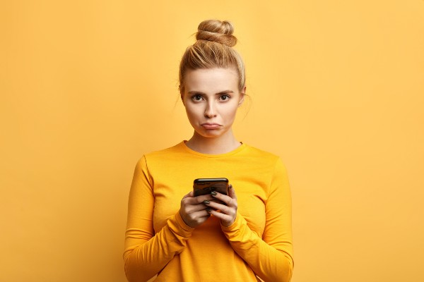 Woman looking sad holding a phone.