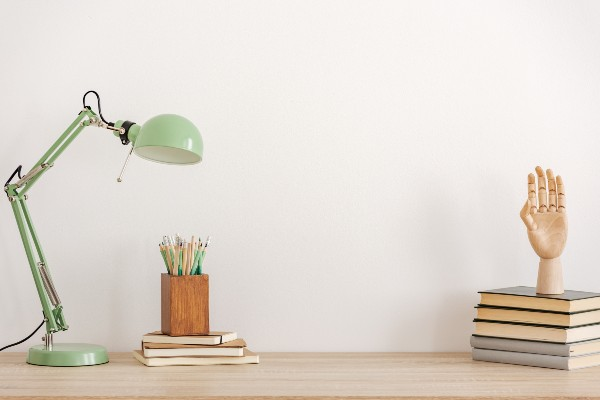 A desk with a lamp, pot of pencils and a stack of books.