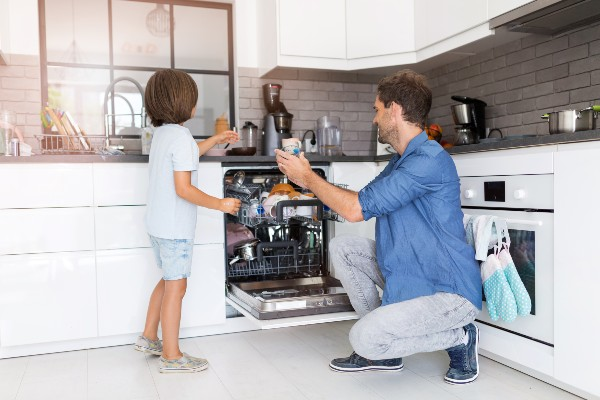 A little boy helping his dad load the dishwasher.