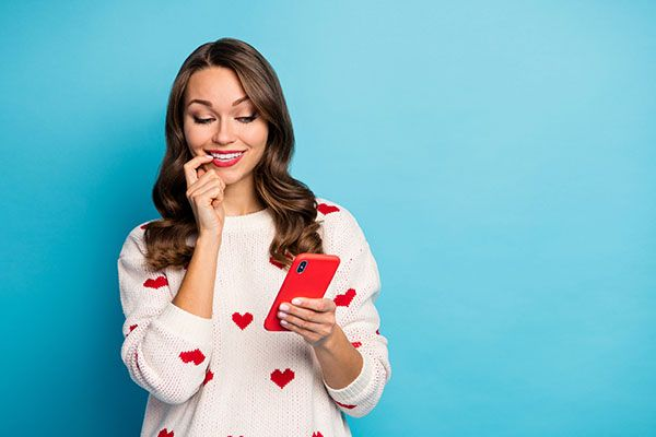 A woman looking at her phone wearing a jumper with a heart pattern