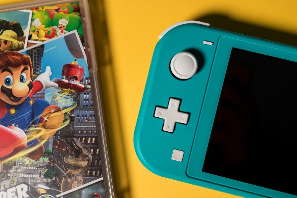A blue Nintendo Switch Lite next to a Mario Switch game