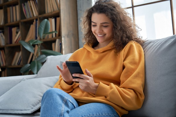 Girl sitting on the sofa playing with her smartphone