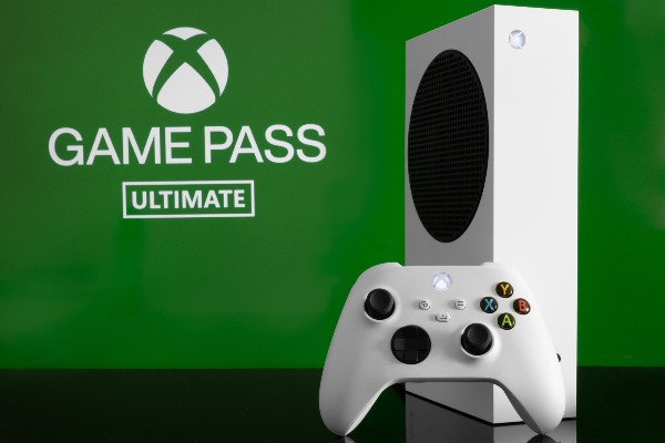 An Xbox Series S in front of an Xbox Game Pass Ultimate sign
