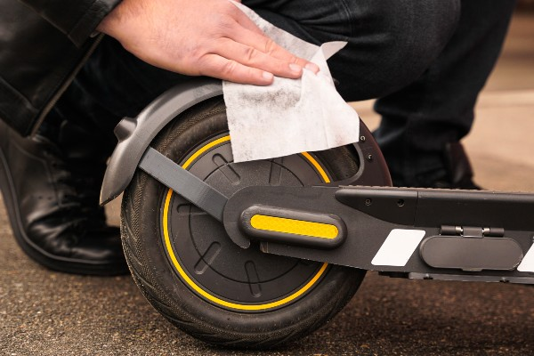 Someone cleaning the wheel of their e-scooter with a wipe