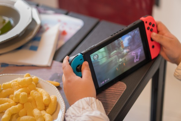 A child sitting at a kitchen table playing a Nintendo Switch with a bowl of crisps next to them