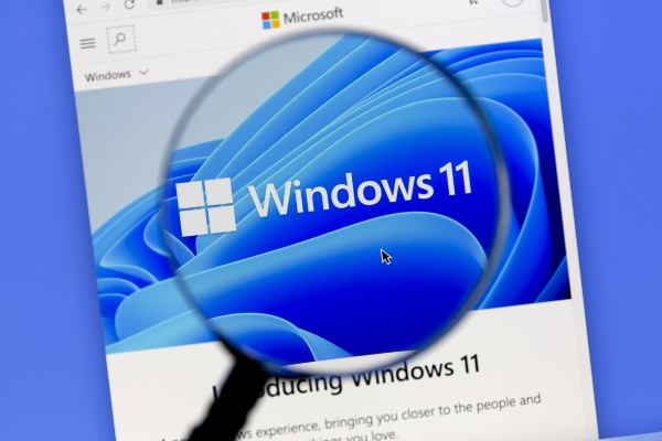 A magnifying glass over a screenshot of Windows 11