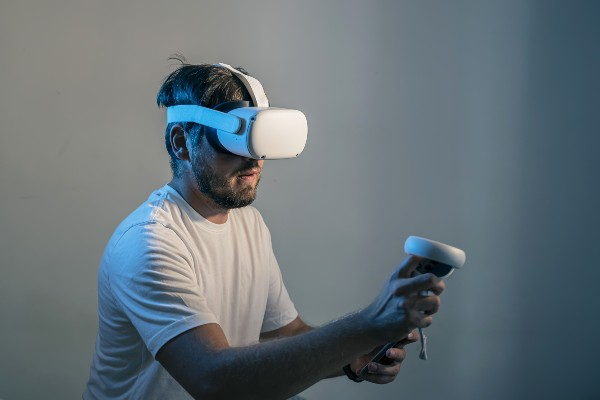 A man playing a VR game with an Oculus Quest 2 headset and controllers