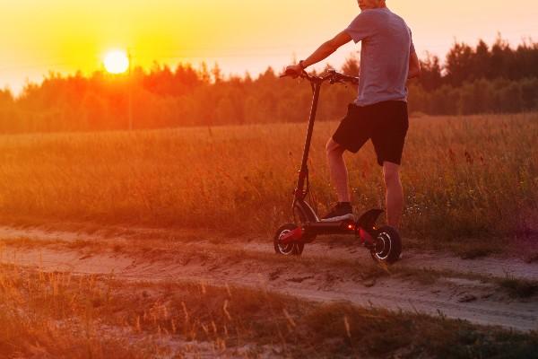 A man riding an e-scooter down a dirt track