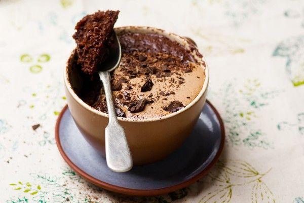 A chocolate mug cake in a brown and blue mug and saucer