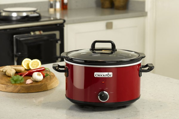A Crock-Pot slow cooker on a kitchen counter next to ingredients