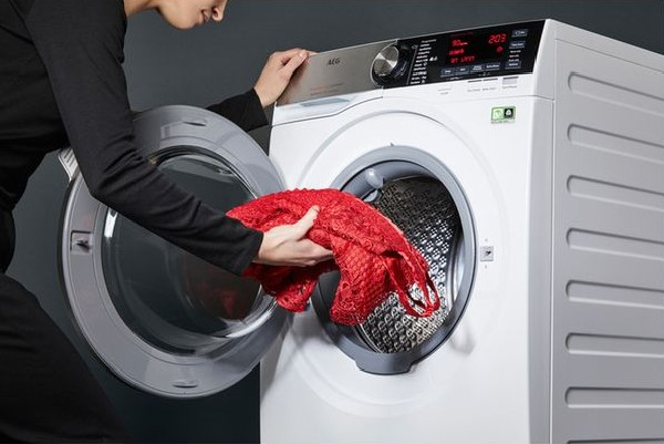 A woman loading laundry into the AEG Soft Water L9FEC966R washing machine.