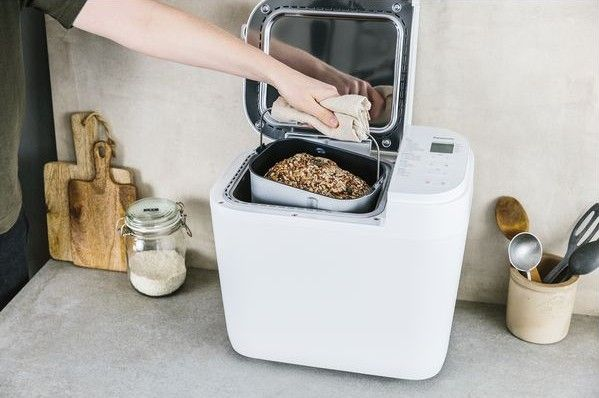 A person pulling dough out of a Panasonic bread maker